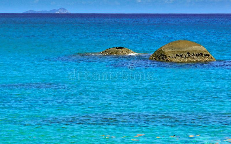 Two round rocks in the turquoise colored waters of the seychelles royalty free stock photos