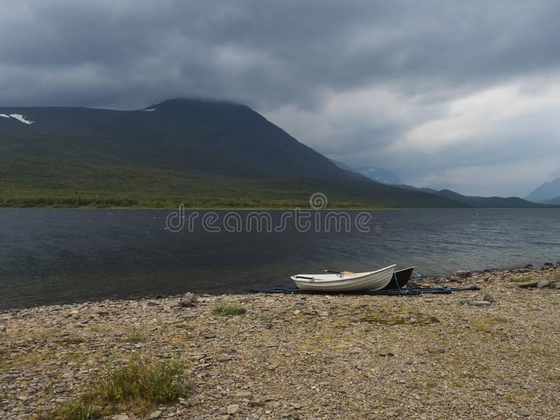 Two rowing boats at Kungsleden hiking trail on bank of Teusajaure lake with birch tree forest and mountains. Lapland nature. Landscape in summer, moody sky royalty free stock photography