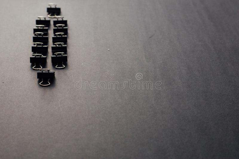 Two rows of black steel paper clips on the left of a black background. One single paper clip on a front and at the back of the rows. Horizontal layout, text royalty free stock image