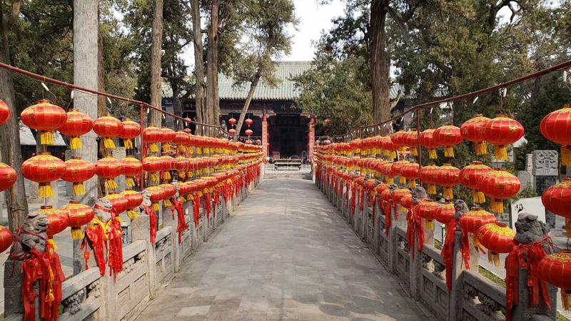 Two rows of stone lions in Guanlin Temple are covered with red lanterns stock image