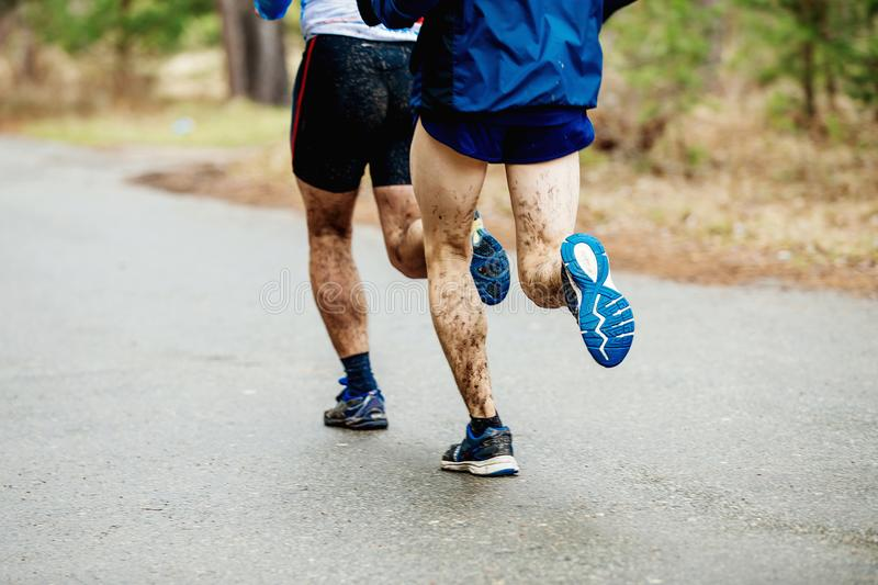Two runners with dirty feet run stock photography
