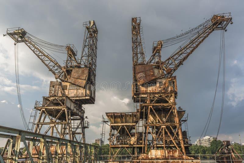 Two rusty, derelict cranes stock photos