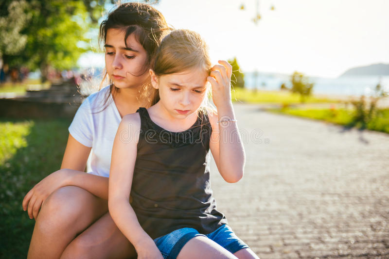 Two sad girls sitting on a bench in park. Two sad young girls sitting on a bench in park by the river royalty free stock images