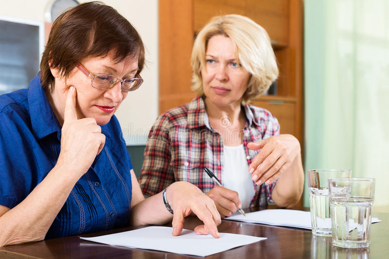 Two sad mature women looking documents. At table stock photography