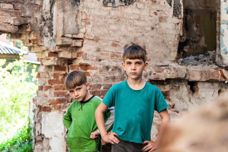 Two sad and unhappy brothers in a destroyed and abandoned building, staged photo.  royalty free stock photography