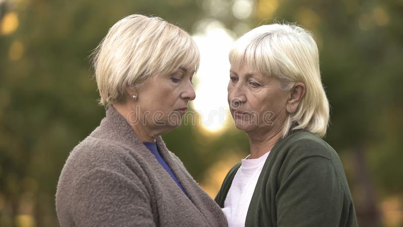 Two sad women with sorrowful eyes supporting each other, family loss, life stock photo
