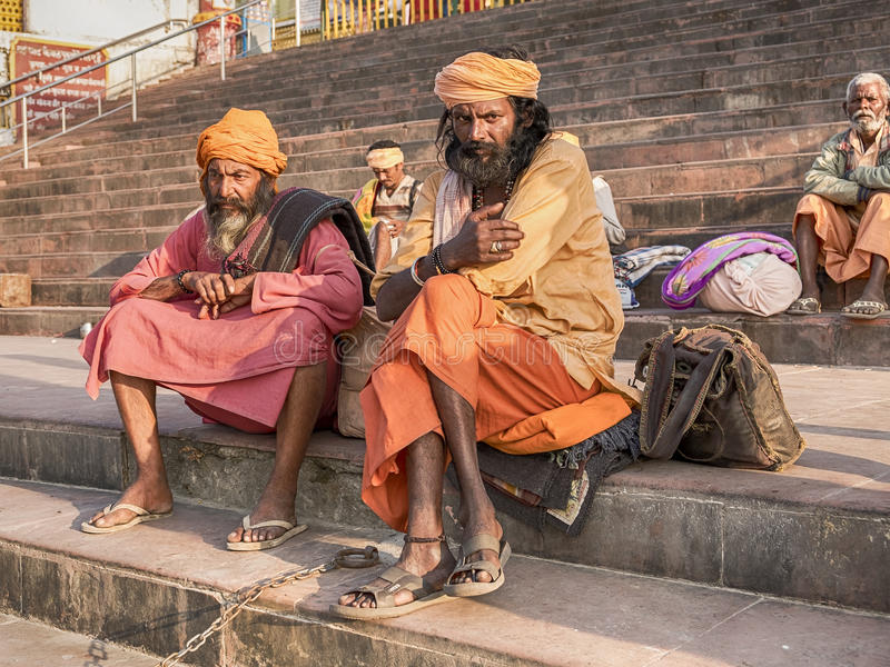 Two Sadhus In Rishikesh. RISHIKESH, INDIA - NOVEMBER 16, 2016: Two sadhus, or holy men, sit in colorful attire the steps of a ghat near the Ganges River in the stock photography
