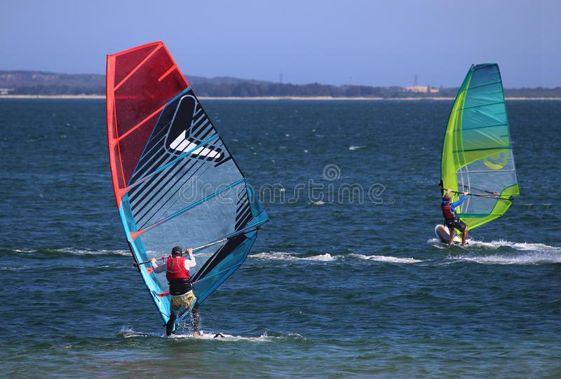 Two sail boarders / wind surfers sailing on the ocean. The horizon in the background royalty free stock photo