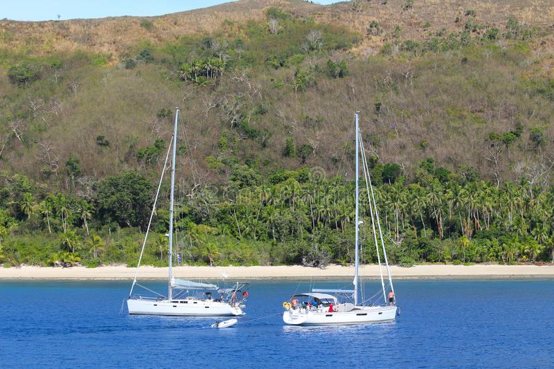 Two sailboats anchored in an island of Fiji royalty free stock images