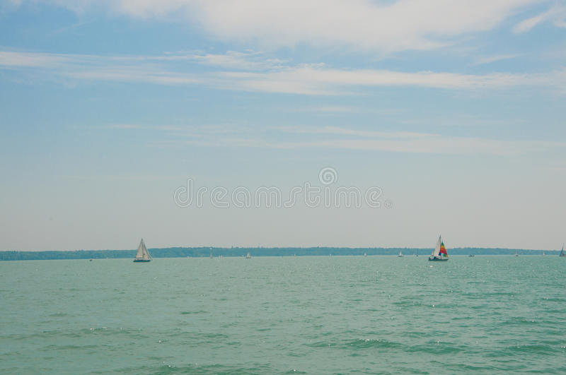 Two sailing boats on foreground under beautiful blue sky with clouds. Yachting competition on Lake Balaton, Hungary. royalty free stock photography