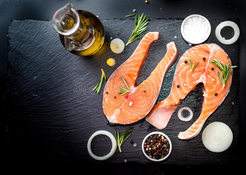 Salmon steak, pepper and salt, herbs on black stone concrete table, copy space top view. Two salmon steak, butter, pepper and salt, lemon, herbs border ,place stock photography