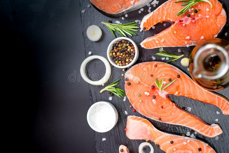 Salmon steak, pepper and salt, herbs on black stone concrete table, copy space top view. Two salmon steak, butter, pepper and salt, lemon, herbs border ,place stock photos