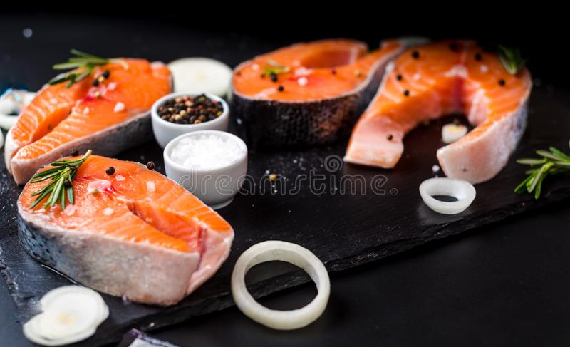 Salmon steak, pepper and salt, herbs on black stone concrete table, copy space top view. Two salmon steak, butter, pepper and salt, lemon, herbs border ,place royalty free stock images