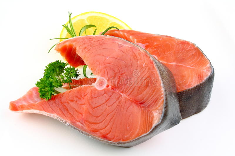 Two salmon steak with lemon, rosemary and parsley royalty free stock image