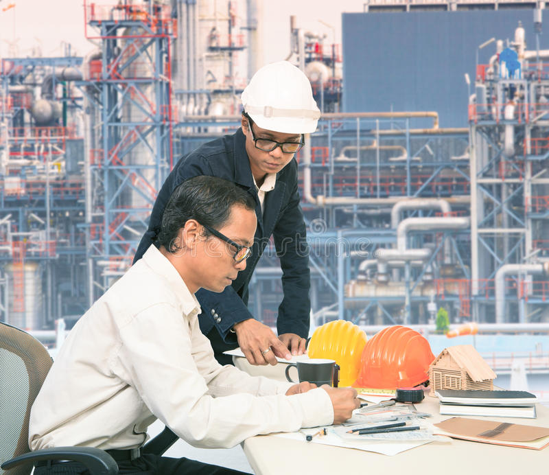 Two of same engineer working on table against exterior of oil refinery p stock photography