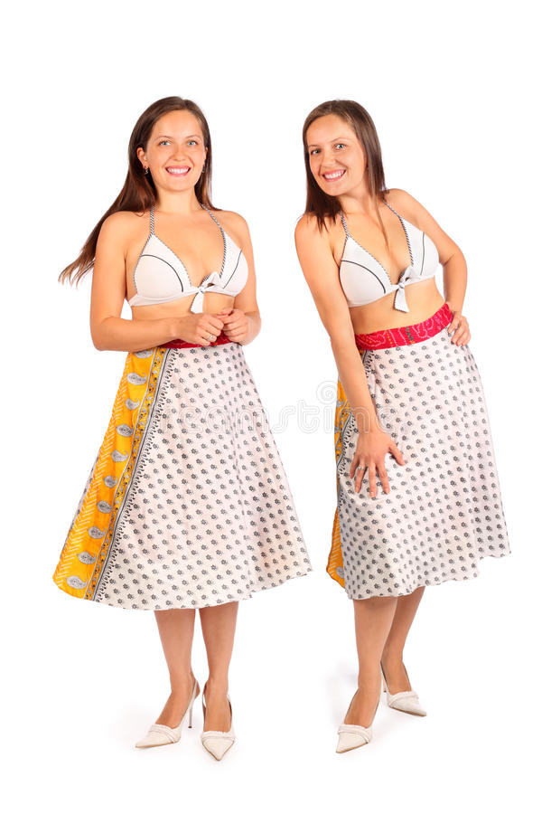 Two same women dressed in bikini and skirt smiles. Two same woman dressed in bikini and skirt smiles in studio on white background stock photos