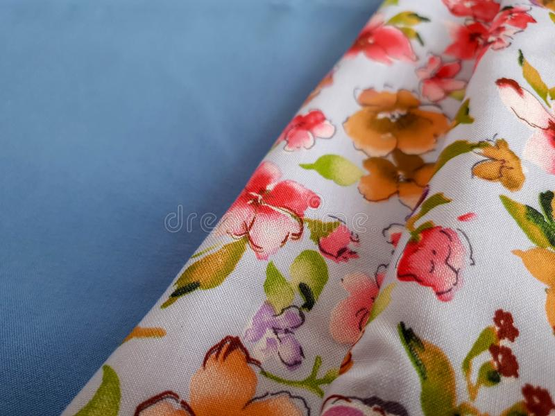 Two samples of blue soft cotton fabric and floral ornament fabric. Sample, pattern, background. ok stock photography