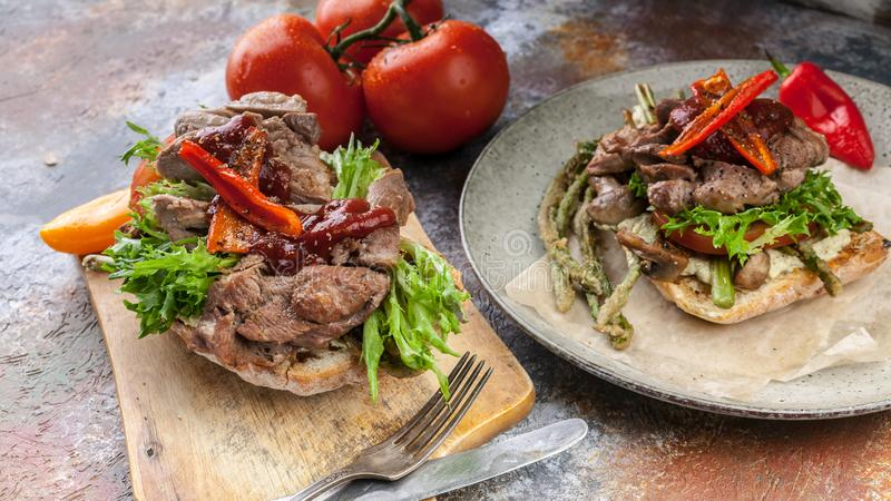 Two sandwiches with turkey meat, mushrooms, sweet peppers, tomatoes and greens on the grill stock images