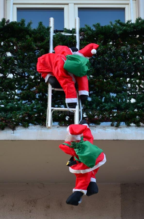 Two Santa Clauses climb at Christmas. Two Santa Clauses climb into the house at Christmas stock images