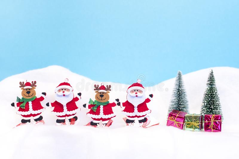 Two Santa Clauses and two reindeer with gifts. In the snow royalty free stock image