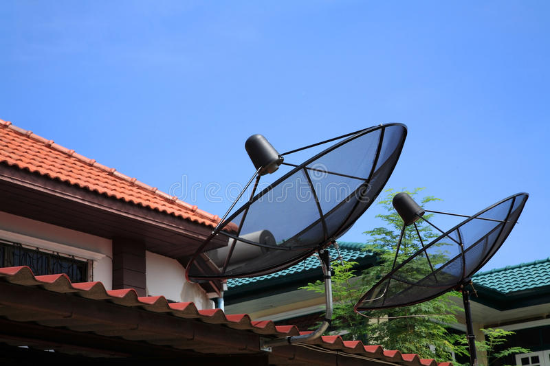 Two satellite dishes mounted on the red roof