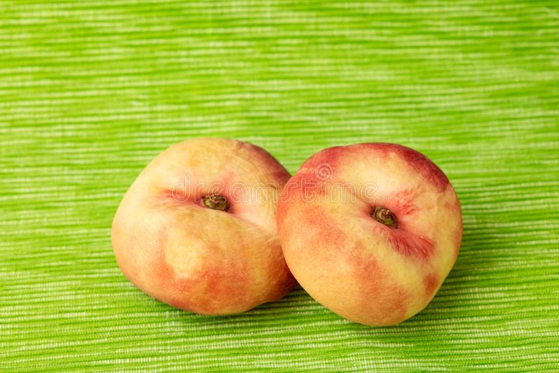 Two saturn peaches from above. Two flat peaches from above on a green background stock photos