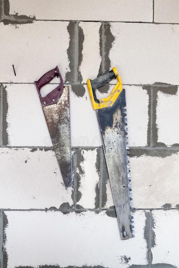 two saws hanging on wall of foam blocks royalty free stock image