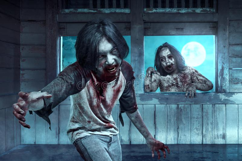 Two scary zombies with blood and wound on his body haunted the old wagon. At night. Halloween concept stock image