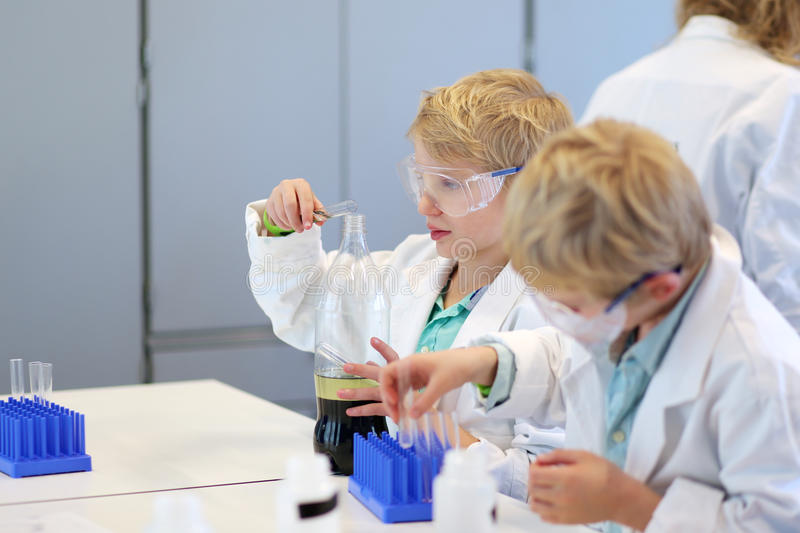 Two school boys during chemistry class. Two secondary school students, smart teenage boys, in safety glasses and white lab coats enjoying their class making royalty free stock photos