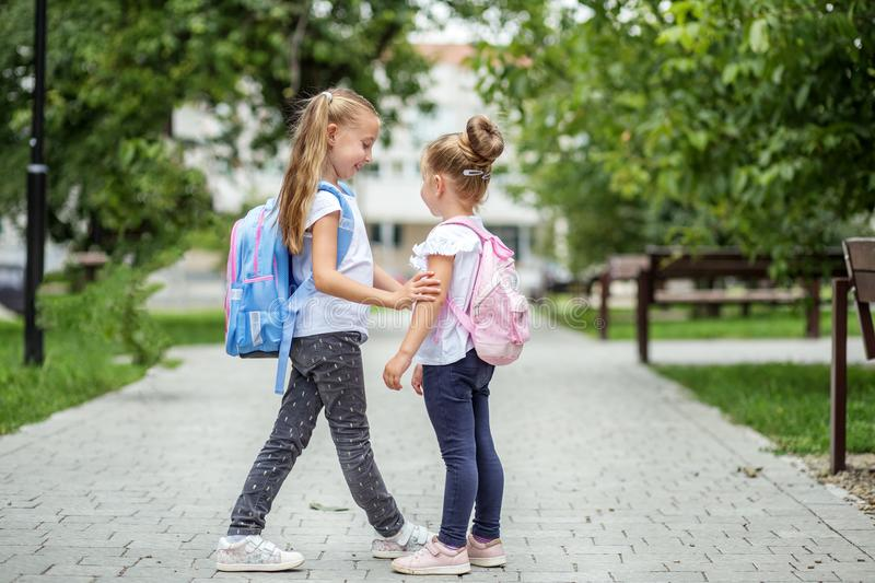 Two school friends met near the school. The concept of school, study, education, friendship, childhood. Two school friends met near the school. The concept of stock photos