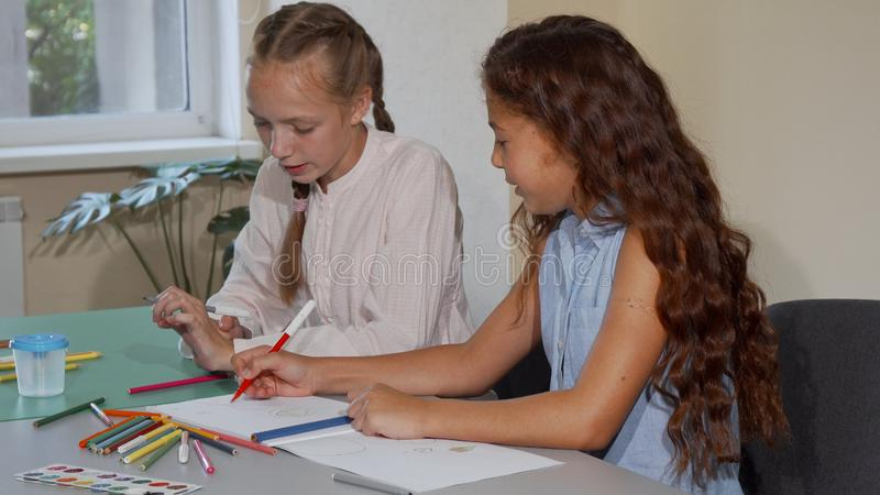 Two school friends talking while drawing together at art class lesson royalty free stock photos