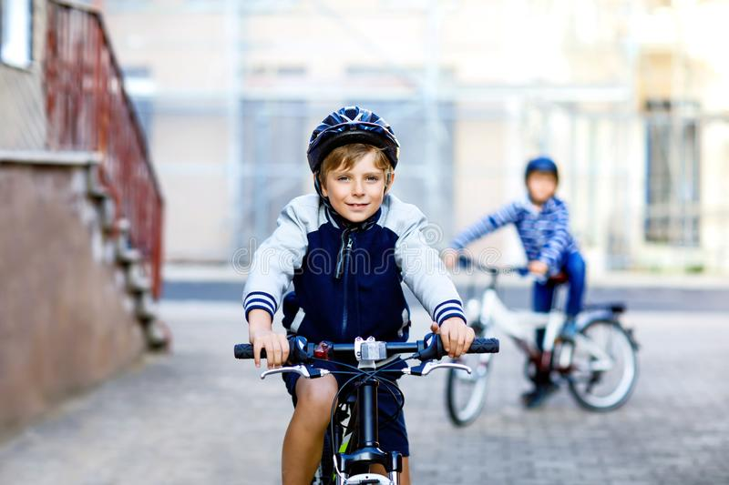 Two school kid boys in safety helmet riding with bike in the city with backpacks. Happy children in colorful clothes royalty free stock photo