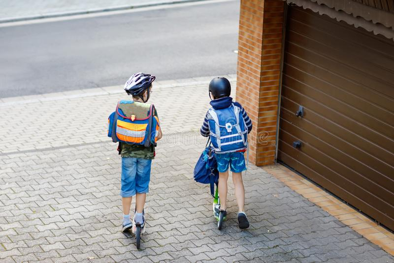 Two school kid boys in safety helmet riding with scooter in the city with backpack on sunny day. Happy children in stock photos