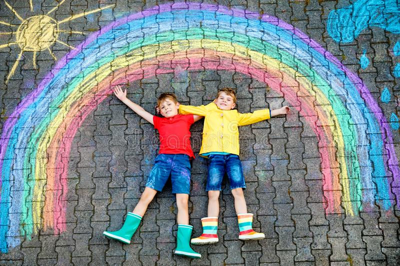 Two school kids boys having fun with with rainbow picture drawing with colorful chalks on asphalt. Siblings, twins and. Best friends in rubber boots painting on stock images