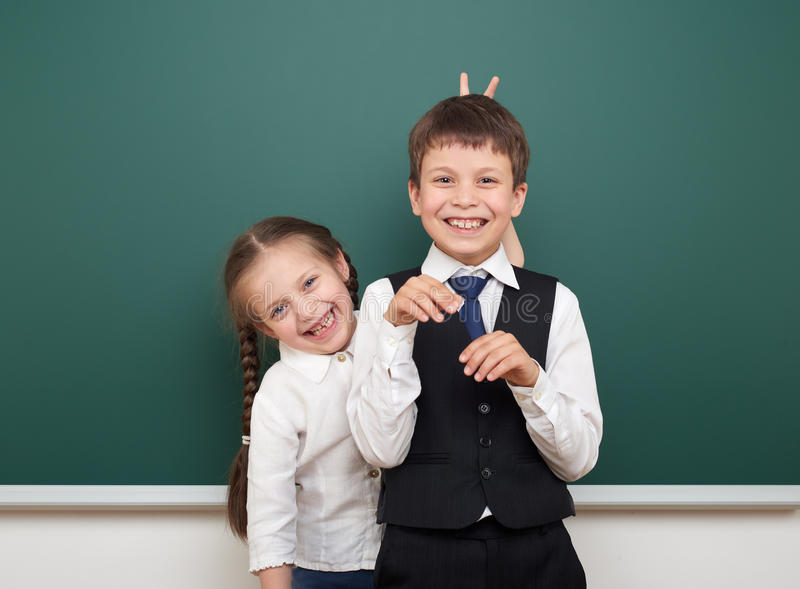 Two school student posing at the clean blackboard, grimacing and emotions, dressed in a black suit, education concept, studio stock images