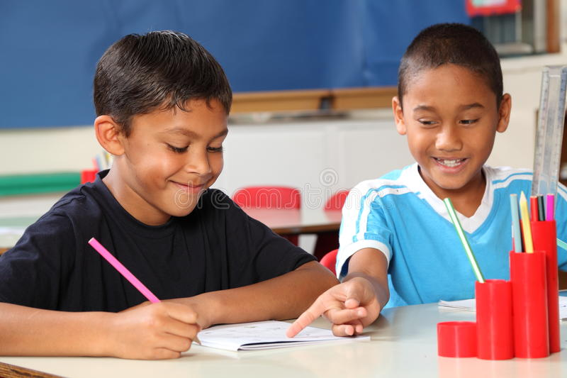 Two schoolboys helping each other learn in class d royalty free stock photography
