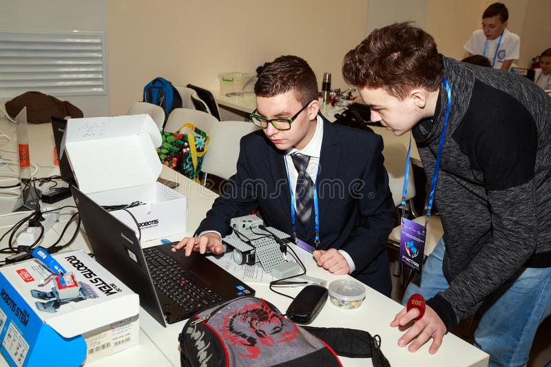 Two schoolboys programming the robot at robotics competitions. royalty free stock photos