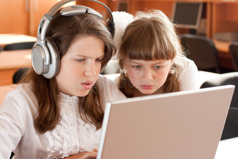 Two schoolgirls concentrated with notebook stock images