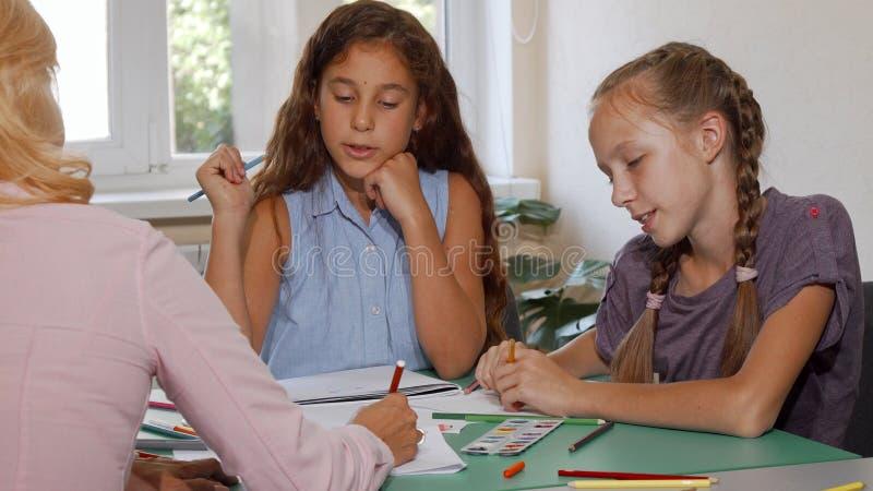 Two schoolgirls enjoying their art class with teacher at school stock image