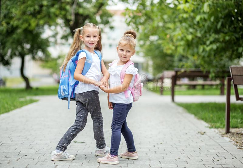 Two schoolgirls go to school. The concept of school, study, education, friendship, childhood. Two schoolgirls go to school. The concept of school, study royalty free stock photos
