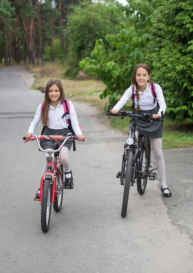 Two schoolgirls riding to school on bicycles. Two beautiful schoolgirls riding to school on bicycles royalty free stock images