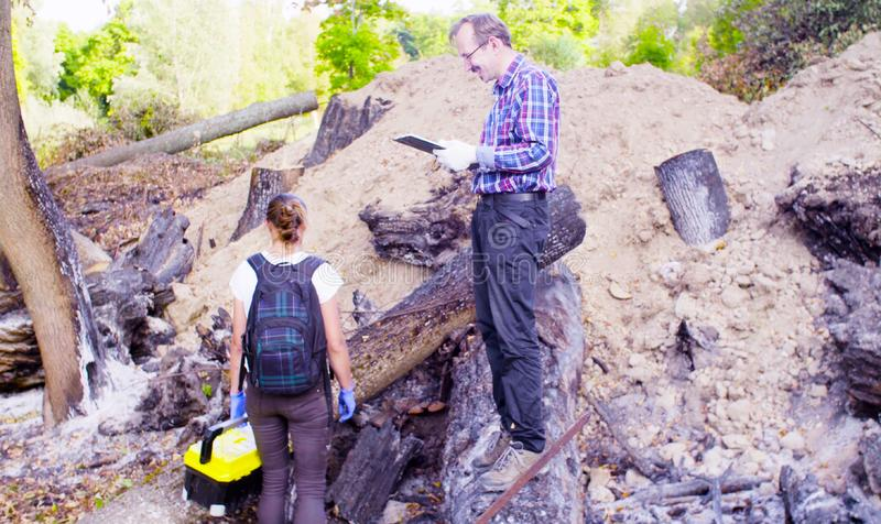 Two scientists ecologists working on place where the forest burned down. Crane shot. Two scientists ecologists working at the place where the forest burned down royalty free stock image
