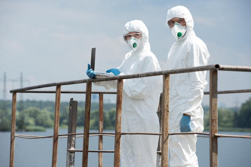 two scientists in protective suits and masks working with laptop and looking at camera near river royalty free stock photo