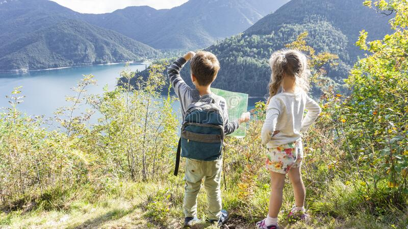 Two scout children stand on a tourist route along a camping road on the shore of a mountain lake Ledro in the Alps. Kids hiking in. Two brave scout children royalty free stock images