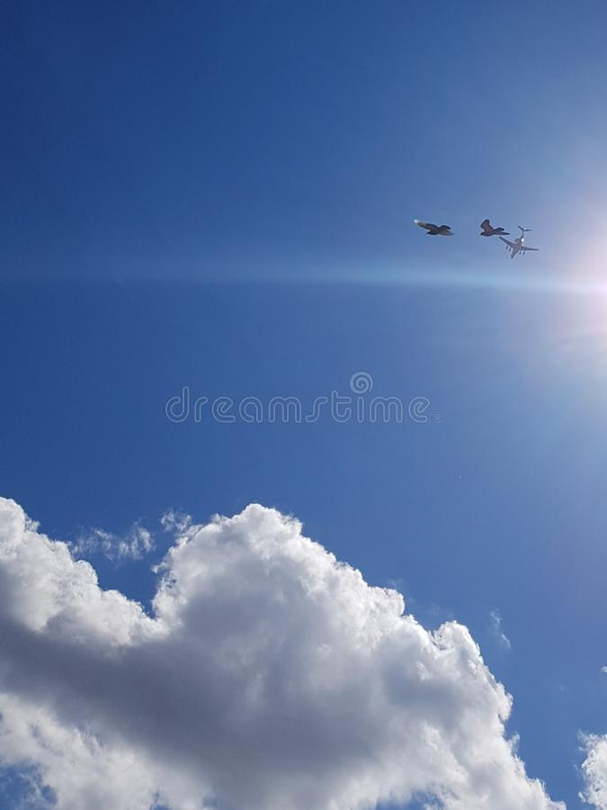 Two seagulls on a summer cloudy day in the sky are flying together behind the plane. stock images