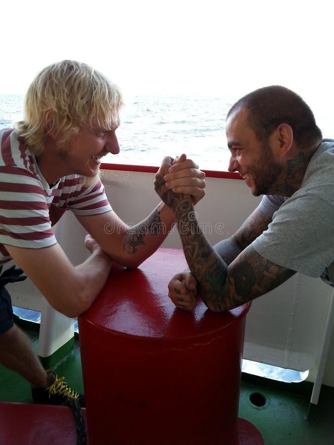 Two seamen are arm wrestling on board of a vessel at sea. Two seamen are arm wrestling for fun on board of a vessel at sea royalty free stock photography