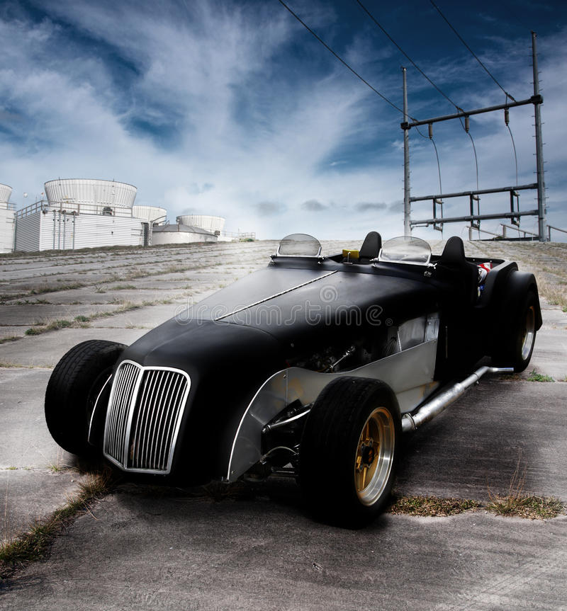 Car roadster classic. A two seater classic roadster black convertible sports car. The vehicle is on a concrete roadway with an industrial backdrop royalty free stock photo