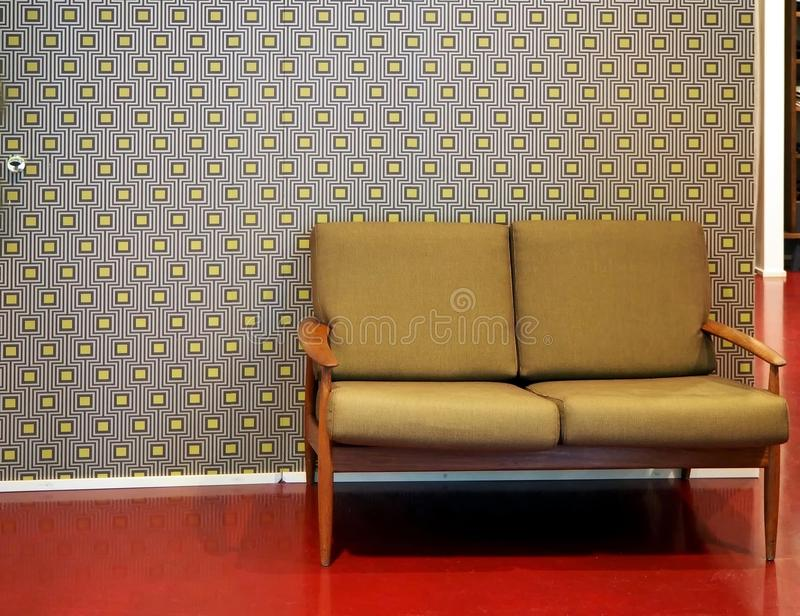 Two-seater retro sofa on red floor. In the background, wallpaper with gray and yellow seamless pattern royalty free stock photography