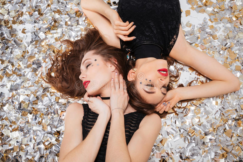 Two seductive beautiful women lying on background of shining confetti. Top view of two seductive beautiful young women with red lips lying on background of stock photos
