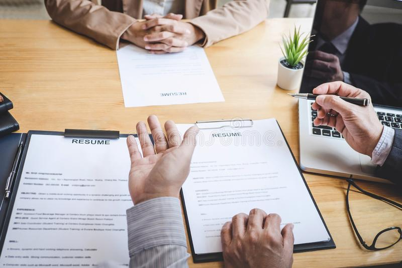 Two selection committee manager reading a resume during a job interview, Employer interviewing to ask young female job seeker for. Recruitment talking in office royalty free stock images